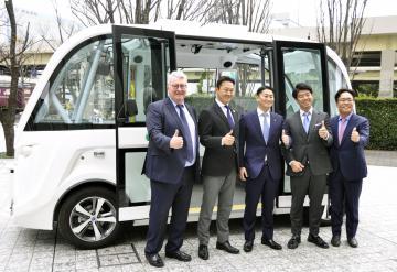自動走行バスの前で記念撮影する境町の橋本正裕町長(中央)ら=東京都港区