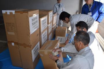 マスクなどの支援物資を梱包する常陸太田市職員=30日午前、同市金井町