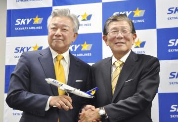 佐山展生会長(左)と握手するスカイマークの洞駿社長=東京都千代田区