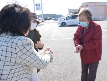 支持者(右)と触れずに両手を組む「エア握手」をする立候補者(左)=阿見町中央