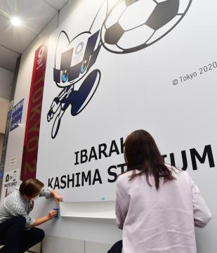 東京五輪延期を受け、サッカー競技の壁面広告に示されていた開催日部分をシールで覆う県職員ら=25日午後、県庁、菊地克仁撮影