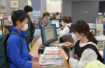 再開した日立市立記念図書館で本を借りたり、返却したりする来館者=同市幸町