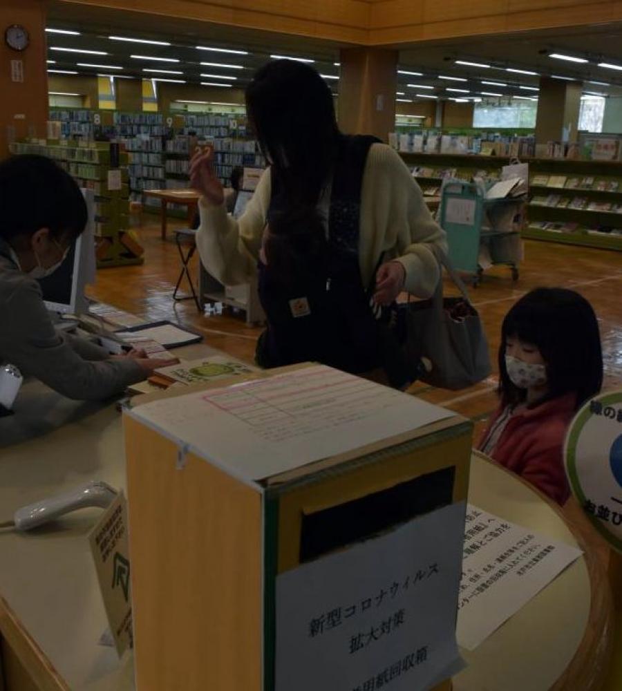 約1カ月ぶりに開館した水戸市立東部図書館で、予約していた絵本を借りる親子=同市元吉田町