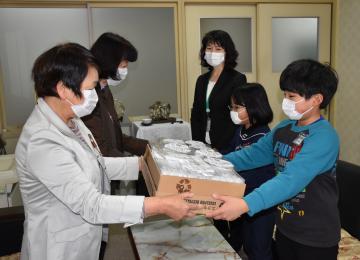 マスクを作ったボランティア代表(左)から児童代表にマスクが手渡された=常陸太田市立佐竹小