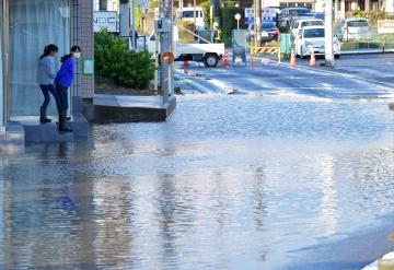 冠水した道路を見つめる人たち=18日午後4時55分、土浦市神立中央