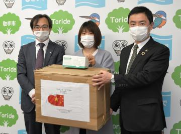 藤井信吾取手市長(右)にマスクを手渡す崔梅花さん(中)と兪明鶴さん=同市役所