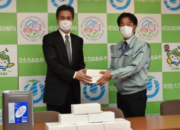 鈴木定幸市長(左)にマスクを手渡す山下起典専務=常陸大宮市役所