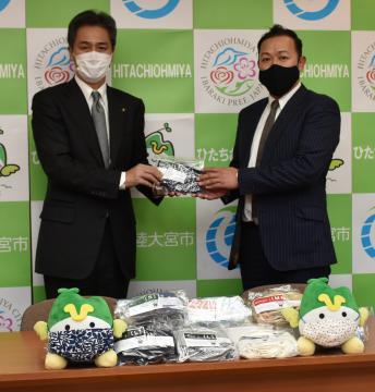 「小中学生に使ってほしい」と、鈴木定幸市長(左)にマスクを手渡す砂川豊朗社長=常陸大宮市役支所