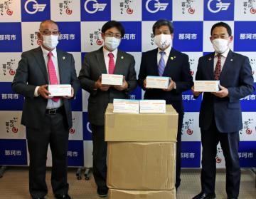 先崎光市長(右から2人目)にマスクを寄贈した小宅清史会長(同3人目)=那珂市役所