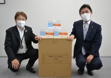 小泉元伸教育長にマスクを手渡す清水建設の清水洋一社長(左)=県庁