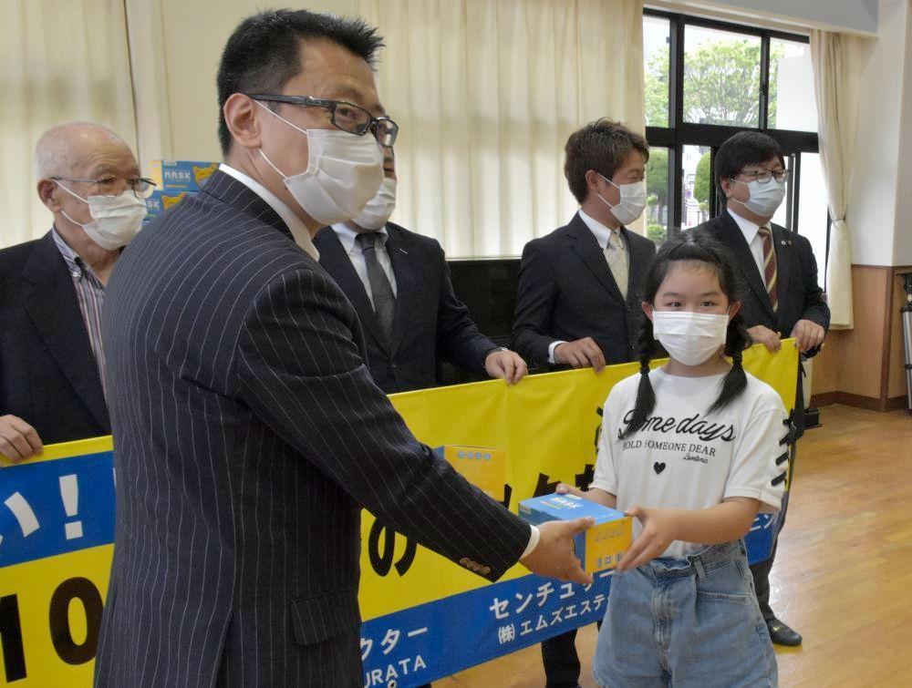 「J&C」の中川周社長(手前左)からマスクを手渡される鈴木花さん=水戸市三の丸の市立三の丸小学校