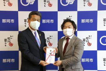 先崎光市長(左)に目録を手渡す「アフターフィット」の谷本貫造代表取締役=那珂市役所
