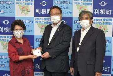佐々木喜章利根町長(中)、海老沢勤町教育長(右)にマスクを手渡す高橋和子さん=同町役場