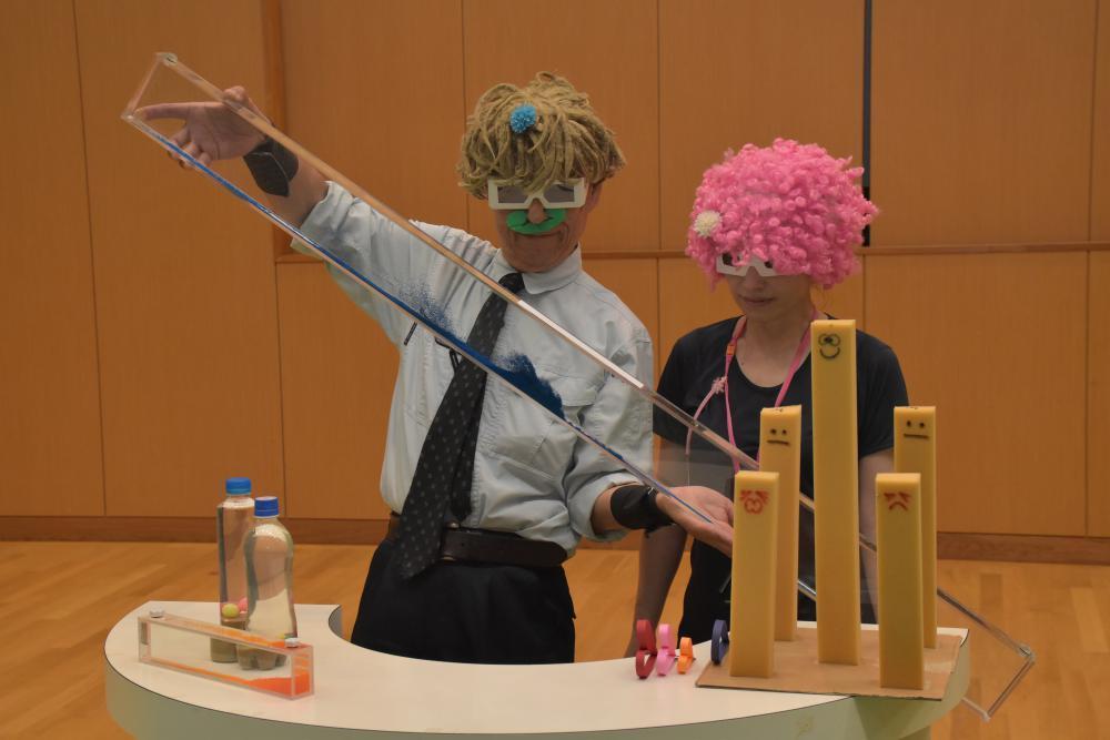 雪崩の仕組みについて実験を披露するナダレンジャーこと納口恭明さん(左)=つくば市天王台