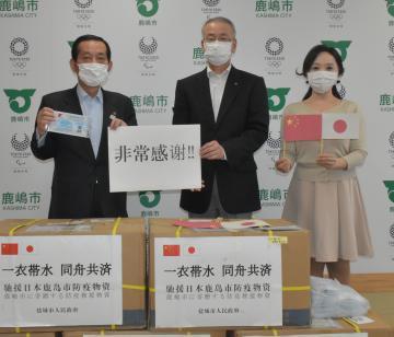 中国・塩城市から届いたマスクに対し、謝意を示す鹿嶋市の錦織孝一市長(左)と市日中友好協会の千葉功会長(中央)=鹿嶋市役所