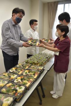 医療従事者に弁当を手渡す「レストラン中台」の中台義浩さん(左)ら=牛久市柏田町