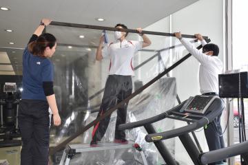 飛沫感染を防ぐための仕切りをランニングマシンに設置する従業員ら=水戸市東原