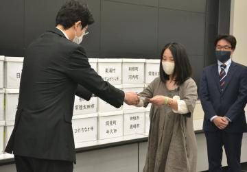 県民投票条例制定請求書を県担当者に手渡す姜咲知子共同代表(右から2人目)=県庁