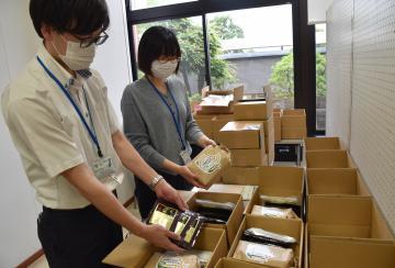 「ふるさと茨城町学生応援便」の箱詰め作業をする町職員ら=茨城町総合福祉センター