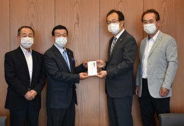 新型コロナウイルス対策として坂東市に10万円を寄付する古河法人会坂東地区会のメンバー=坂東市役所