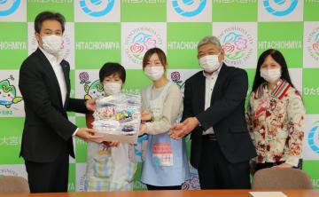 鈴木定幸市長(左)に子ども用の手作りマスクを寄贈する後藤悟子理事長(右端)ら虹のポケットのスタッフ=常陸大宮市役所