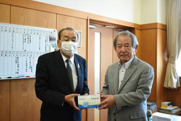 鈴木博光校長(右)にマスクを手渡す白梅商事の市毛勝利会長=水戸市千波町