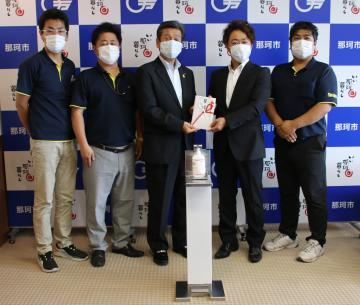先崎光市長(中央)に目録を手渡す石川尚史社長(右から2人目)=那珂市役所