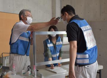 新型コロナウイルス感染対策を踏まえた災害時の避難所運営訓練で、避難者の体温を測る市職員