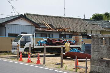 強風で飛ばされたトタン屋根を片付ける作業員ら。奥側の民家では屋根の一部が壊された=那珂市瓜連