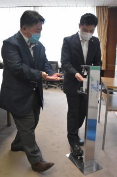 大谷明市長(右)に足踏み式消毒液スタンドの使い方を説明するGLITの松木徹代表=ひたちなか市役所