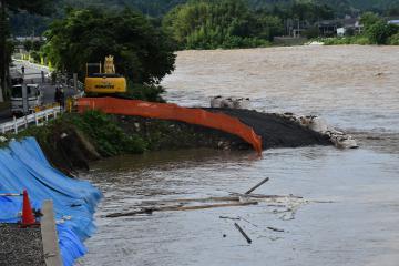 増水して茶色く濁り、流木が目立つ久慈川。台風19号で壊れた堤防の復旧工事が続いている=大子町池田の池田橋付近