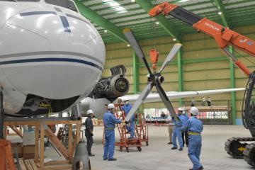 戦後初の国産旅客機「YS11」の組み立てで、左主翼のエンジンにプロペラを取り付ける作業員ら=筑西市茂田