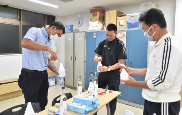 アルコール消毒液の準備をする県高野連の役員ら=ノーブルホーム水戸