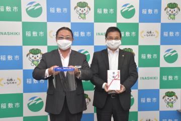 不二プラスチックの池下龍一郎社長(左)から稲敷市にフェースシールドが贈られた=同市役所