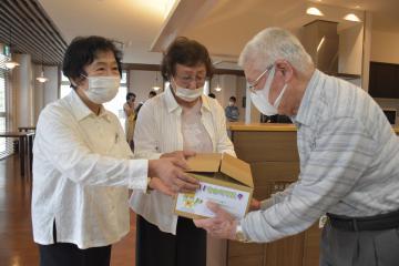 反射材付きの手作りマスクを手渡すひたちなか市高齢者クラブ連合会女性部の(左から)岸弘子さん、渡辺千枝子さん=同市烏ケ台