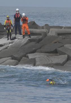 訓練でヘッドランド近くの離岸流に逆らって泳いだものの、沖に流される海上保安庁の特殊救難隊員(手前)=鉾田市玉田