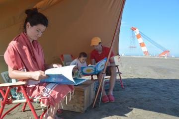 「砂浜図書館」で読書を楽しむ家族=大洗町の大洗サンビーチ