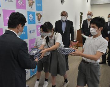 高橋靖市長(手前)にマスクケースが入った箱を手渡す(左から)大山凜人君と弓野ほのかさん、浅川琉生君=水戸市役所