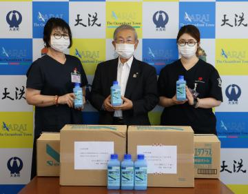 大洗町の小谷隆亮町長(中央)に消毒液を手渡したねもと薬局グループの根本ひろ美代表(左)ら=大洗町役場