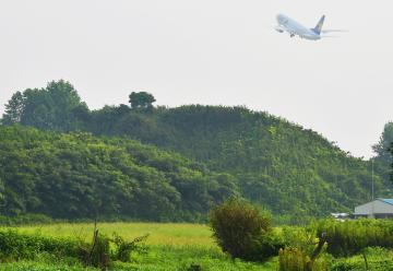 戦闘機が機銃を試射した射撃場跡の土塁(奥)。今は上空を旅客機が飛び交う=小美玉市山野の百里原海軍航空隊跡