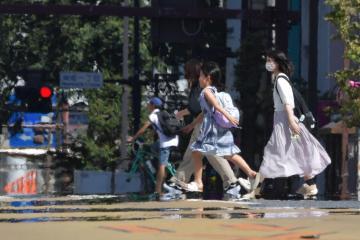 猛烈な日差しでかげろうと逃げ水が発生し、風景が揺らぐ中を歩く人たち=11日午後、水戸市南町