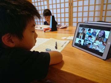 自宅から2日の「オンライン自主学習会」に参加した大橋一葵君(手前)、茉央さん。進行役の安田歩さんから「こんな面白い記事があったよ」と新聞紹介もあった=笠間市内