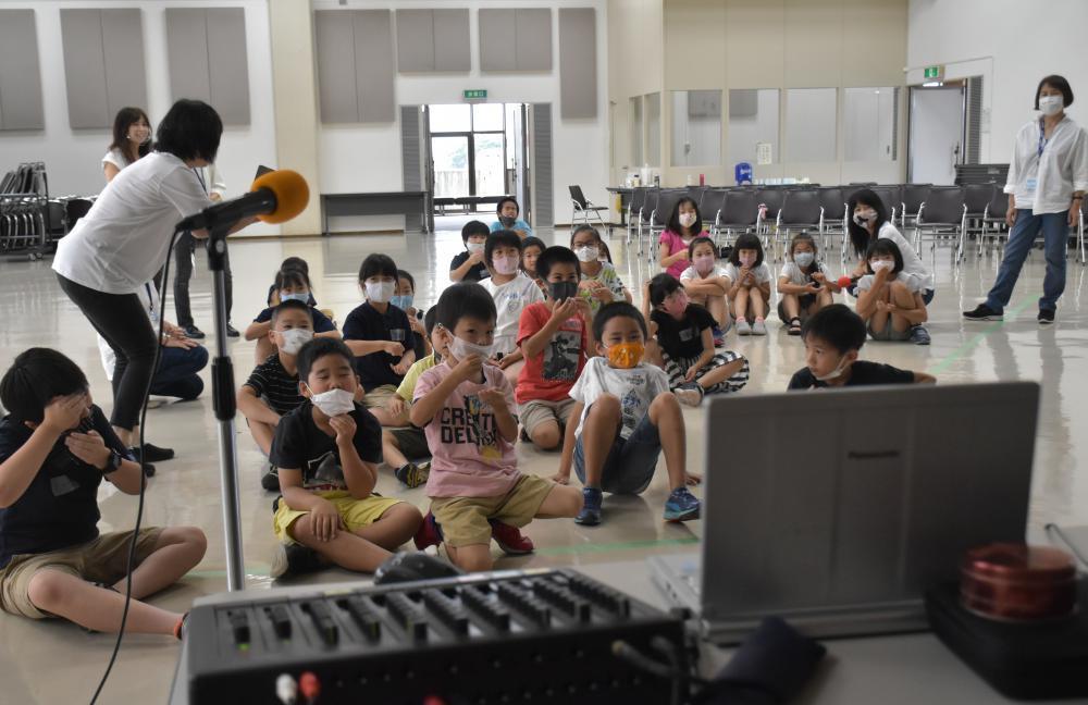 講師がいる東京の会場に向け、ジェスチャーでかき氷を食べる様子を見せる児童ら=水戸市五軒町
