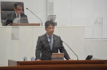 飛沫防止用のアクリル板に囲まれた演壇で提案説明を行う大井川和彦知事=県議会本会議場