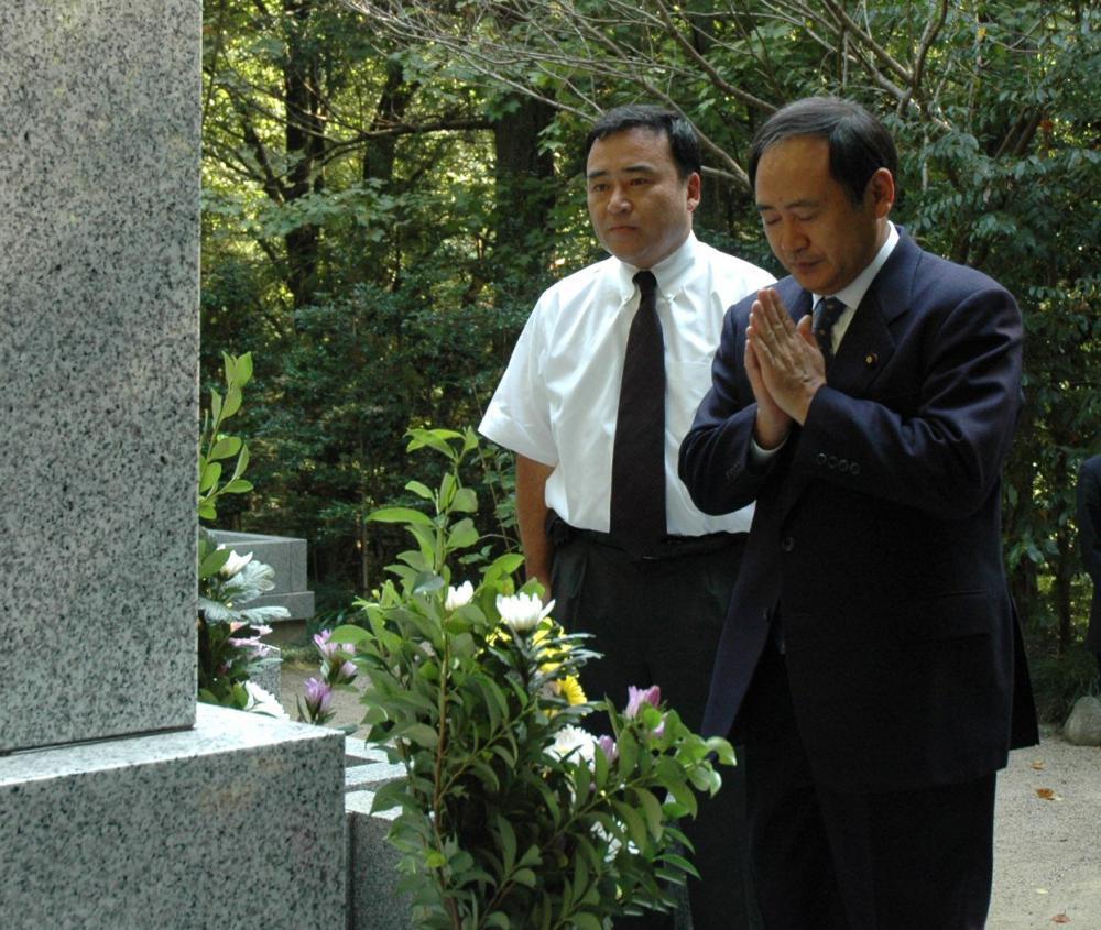 梶山静六氏の墓前に初入閣の報告をする菅義偉総務相(右)。左は梶山弘志国交政務官(肩書きはいずれも当時)=2006年9月30日、常陸太田市内