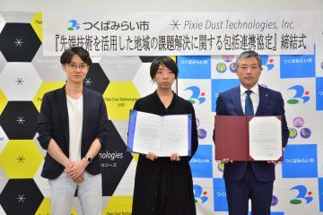 包括連携協定を締結した小田川浩市長(右)とピクシーダストテクノロジーズの落合陽一最高経営責任者(中央)=つくばみらい市役所伊奈庁舎