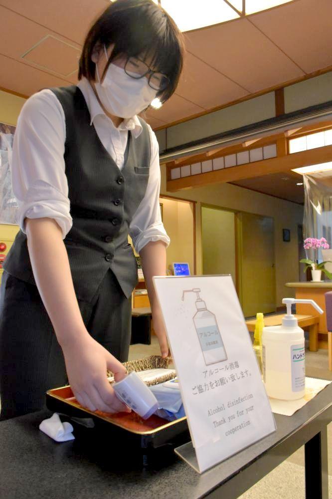 旅館ロビーでマスクや検温機器を準備する豊年万作の従業員=大子町袋田