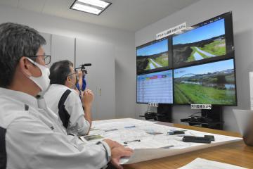 被災地上空を飛行するドローンの位置などについて指示を送る担当者=県庁