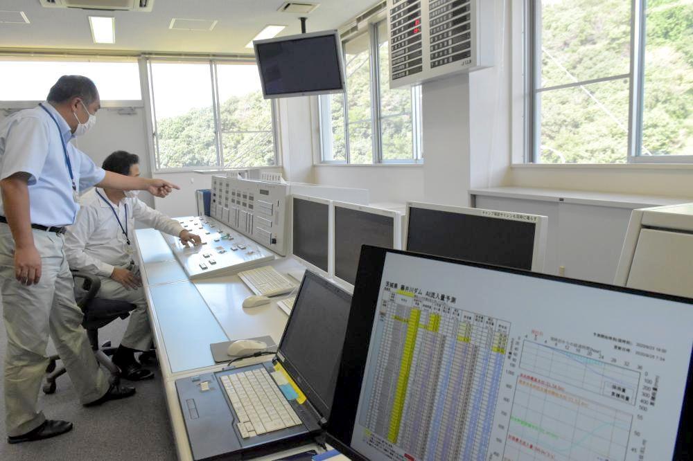 AIによる流入量予測に基づいた事前放流のため、藤井川ダムのゲートの試行操作を行う担当者=城里町下古内