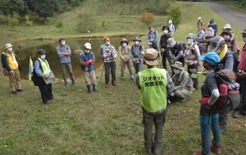 助川山市民の森内の「石の池」で地層などの説明を聞く参加者=日立市諏訪町